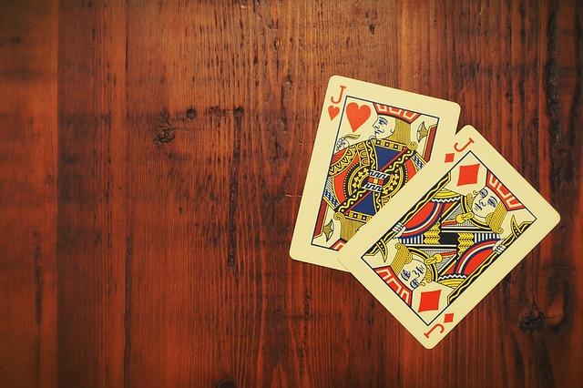 Zwei rote Spielkarten auf einem hölzernen Untergrund.